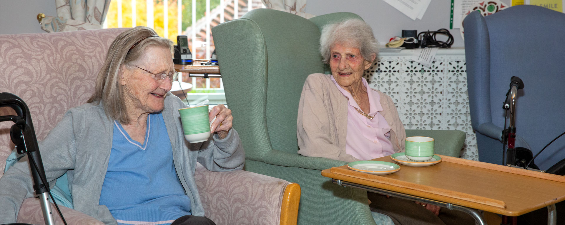 Two residents relaxing in the lounge having a cup of tea