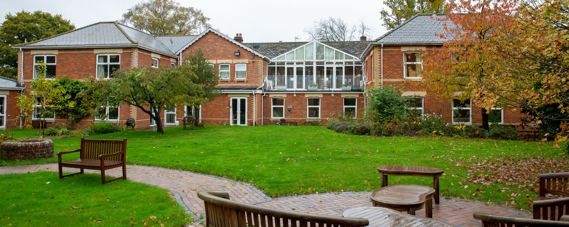 Back view of the care home and gardens with autumn leaves everywhere