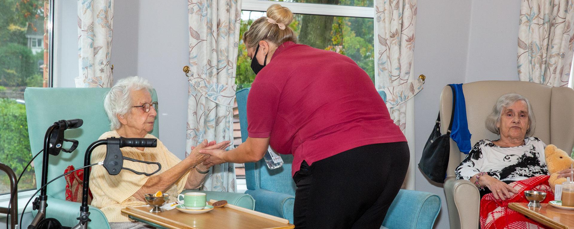 Activity coordinator giving resident hand sanitiser before playing skittles