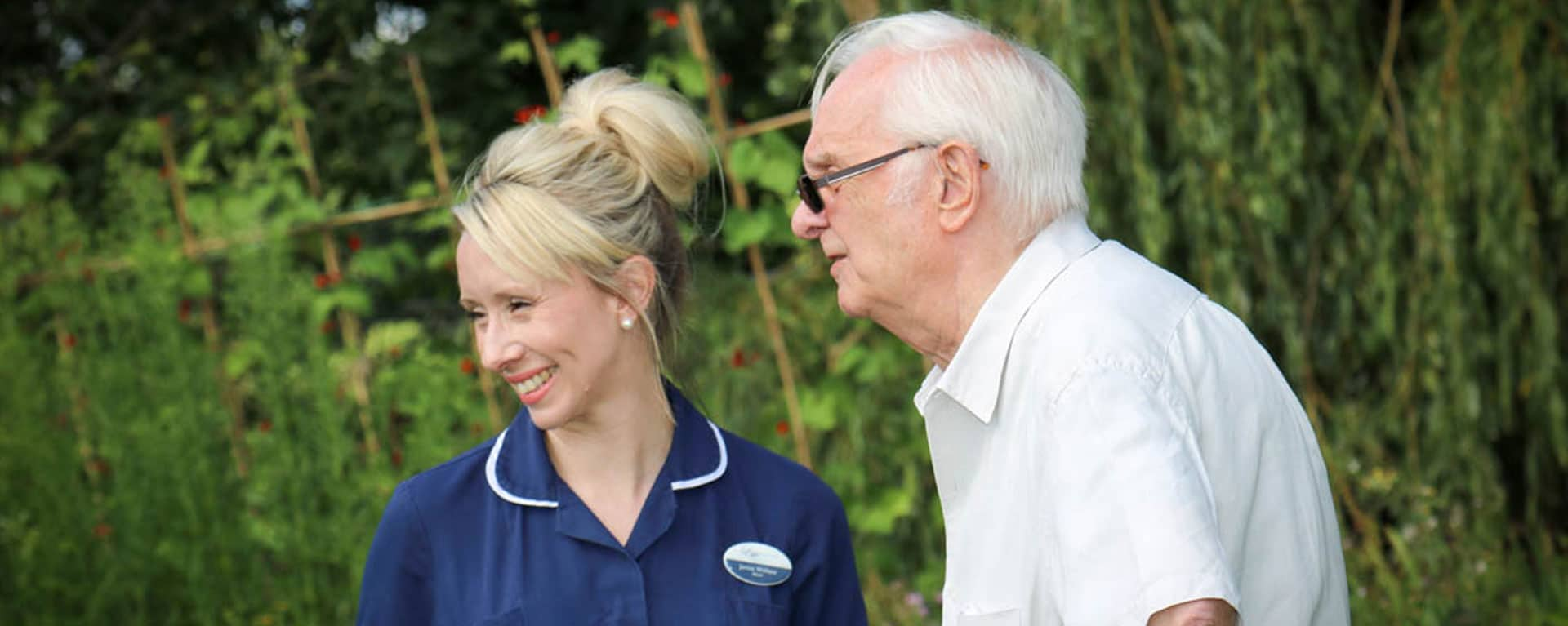 Nurse and resident having a chat in the garden