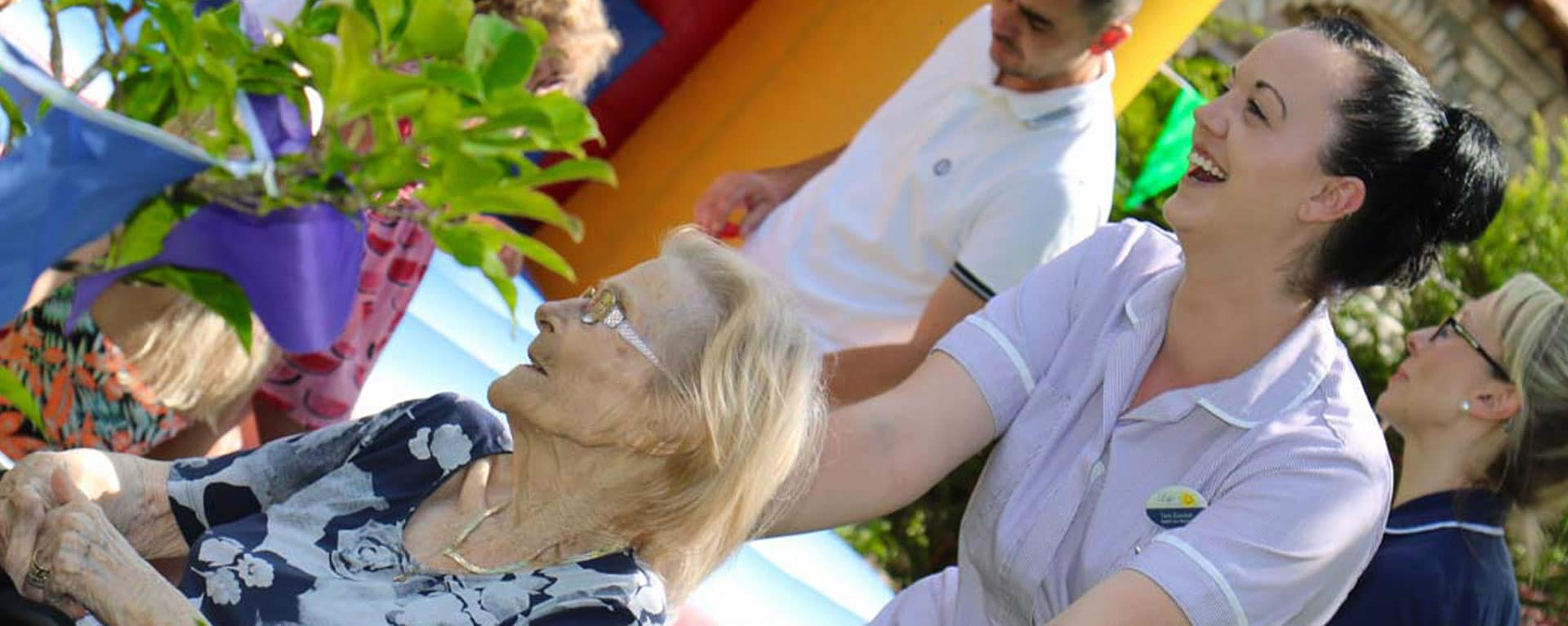 Resident being pushed through Laurel Care Homes fete laughing