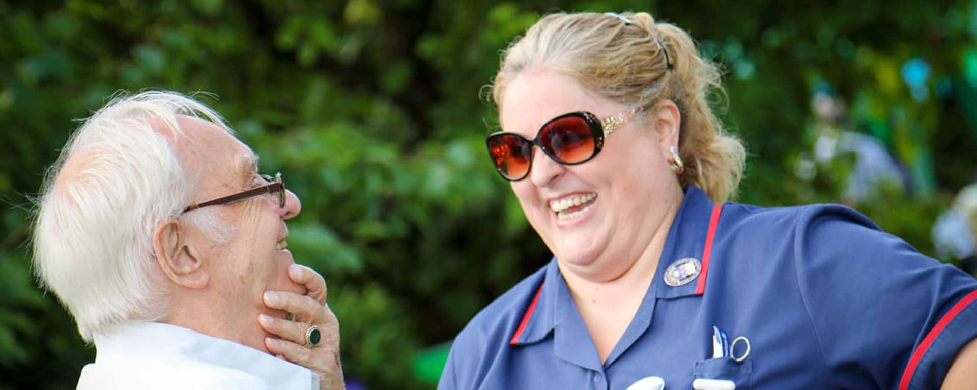 Register Care Home manager and resident laughing in the garden