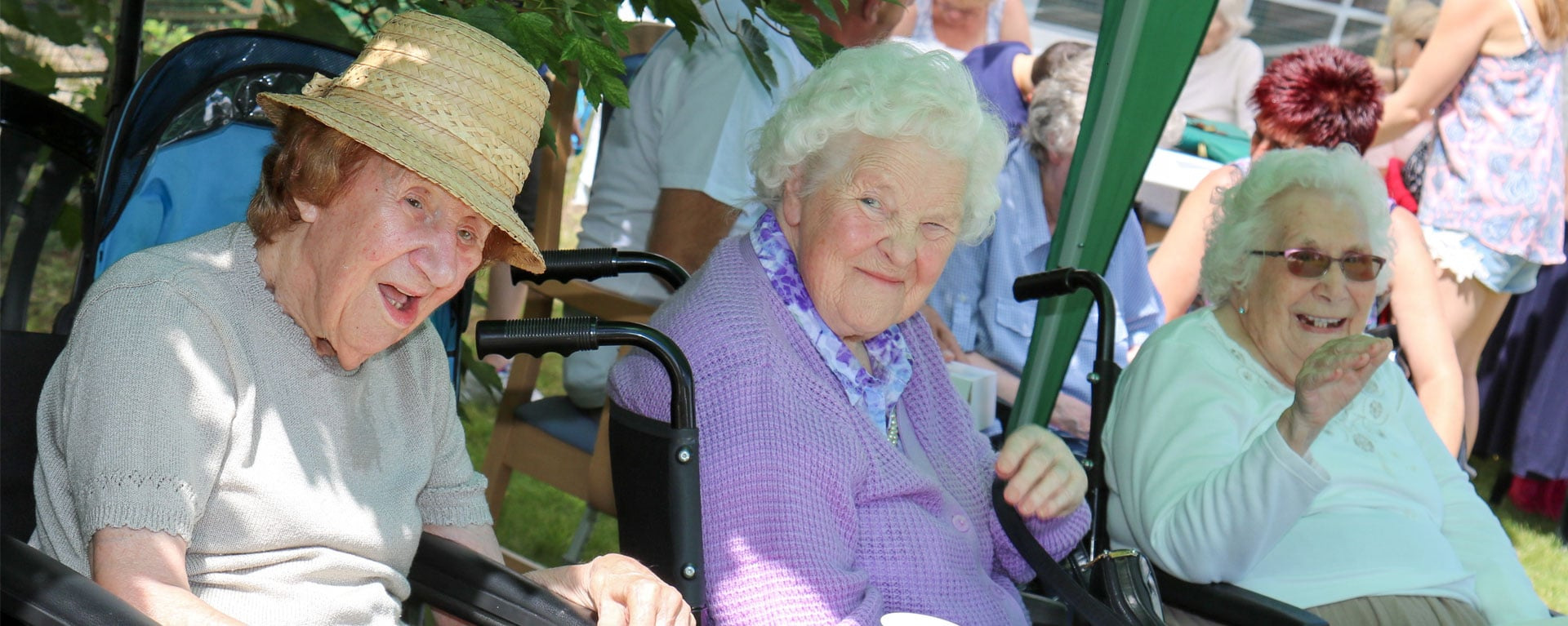 Three residents smiling and laughing at Laurel Care homes summer fete