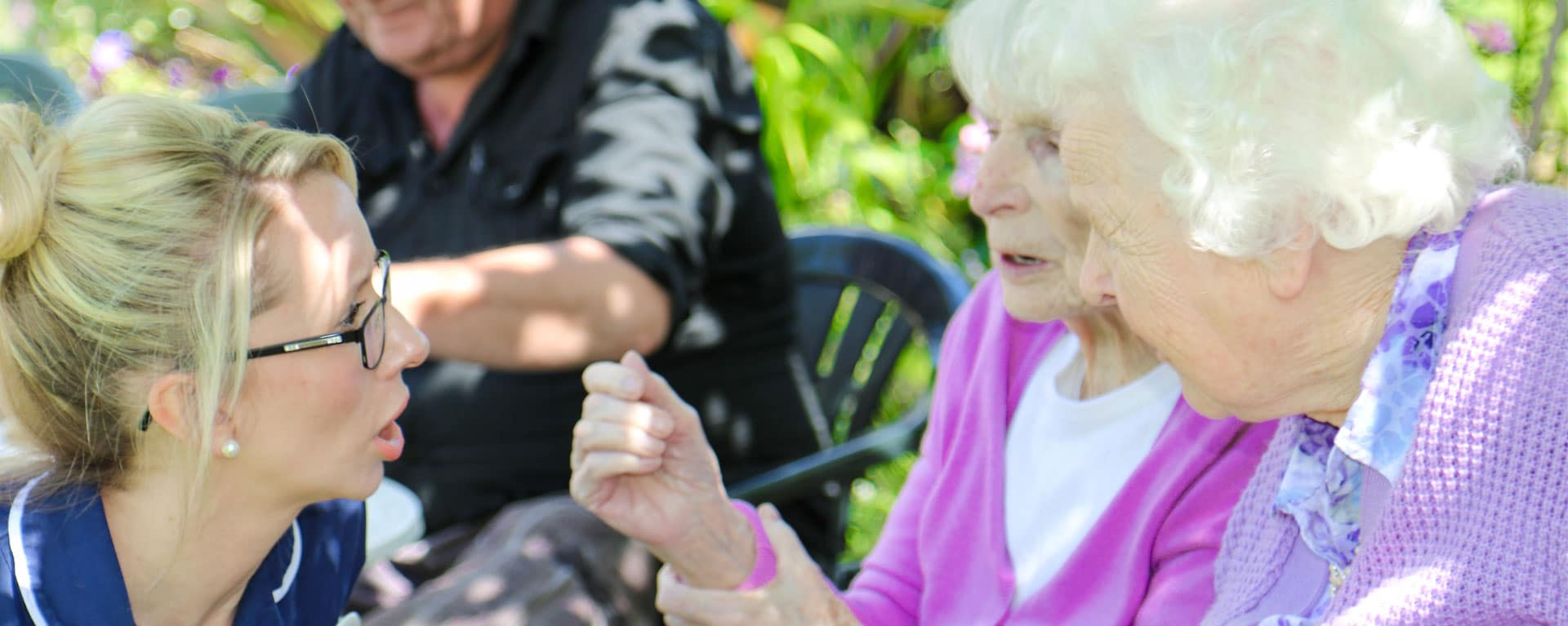 Laurel Care Home nurse helping two residents in the garden