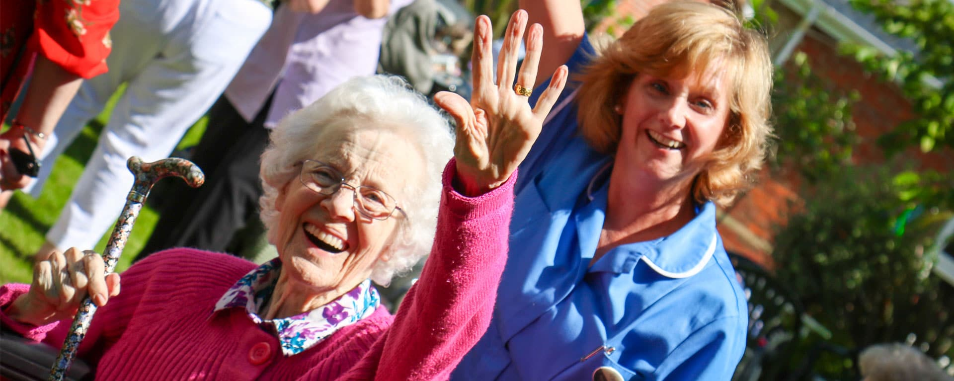 Resident and nurse waving and smiling in the garden